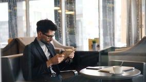 Páginas de torneado inteligentes del libro de lectura del hombre de negocios que se sientan en café solamente almacen de metraje de vídeo