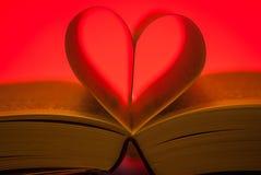 Páginas de un libro que forma un corazón en fondo rojo Fotografía de archivo libre de regalías