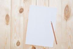 Páginas del álbum con los lápices para dibujar en una tabla Fotografía de archivo