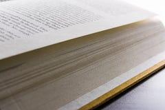 Páginas del libro que atan la lectura de la espina dorsal que mueve de un tirón el escritorio negro de las nuevas palabras brilla Imagenes de archivo