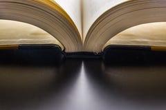 Páginas del libro que atan la lectura de la espina dorsal que mueve de un tirón el escritorio negro de las nuevas palabras brilla Foto de archivo