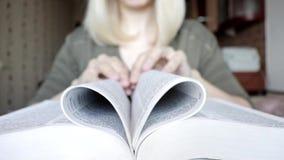 Páginas rubias irreconocibles borrosas en una forma del corazón, concepto de lectura del libro de plegamiento de la mujer del amo almacen de video