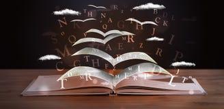 Páginas y letras que brillan intensamente que vuelan de un libro Fotos de archivo libres de regalías