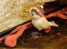 Pájaro de madera tallado con el sombrero de la Navidad que se sienta entre la Navidad que envuelve y que adorna los materiales Imágenes de archivo libres de regalías