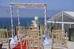 Pájaro que vuela sobre el océano azul, casandose el Gazebo, sillas de madera Fotos de archivo