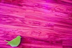 Pájaro verde en superficie rosada Imagenes de archivo