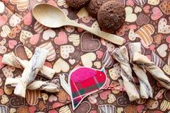 Pájaro y galletas rojos del juguete en servilleta oscura con la imagen de corazones Fotos de archivo libres de regalías