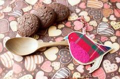 Pájaro y galletas rojos del juguete en servilleta oscura con la imagen de corazones Fotografía de archivo
