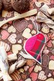 Pájaro y galletas rojos del juguete en servilleta oscura con la imagen de corazones Imagen de archivo