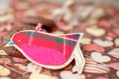 Pájaro y galletas rojos del juguete en servilleta oscura con la imagen de corazones Imagenes de archivo