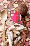 Pájaro y galletas rojos del juguete en servilleta oscura con la imagen de corazones Foto de archivo
