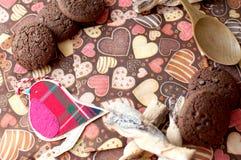 Pájaro y galletas rojos del juguete en servilleta oscura con la imagen de corazones Fotos de archivo