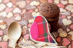 Pájaro y galletas rojos del juguete en servilleta oscura con la imagen de corazones Imágenes de archivo libres de regalías