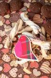 Pájaro y galletas rojos del juguete en servilleta oscura con la imagen de corazones Imagen de archivo libre de regalías
