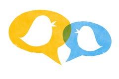 Pájaros con las burbujas amarillas y azules del discurso Foto de archivo libre de regalías