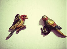Pájaros de madera tallados pintados en las paredes del yeso Fotografía de archivo