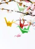 Pájaros de papel coloridos de la papiroflexia en ramas florecientes de la cereza Imágenes de archivo libres de regalías