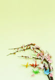Pájaros de papel coloridos de la papiroflexia en ramas florecientes de la cereza Imagenes de archivo