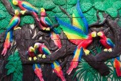 Pájaros en figura tropical de la selva en la pared Imagen de archivo