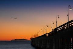 Pájaros que vuelan a casa en la puesta del sol por el embarcadero Imagenes de archivo
