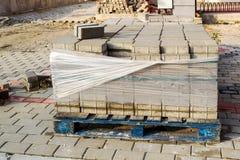 Pálete de madeira com as pedras cinzentas do pavimento no local dos trabalhos de estrada Reparo do passeio em uma rua da cidade fotografia de stock royalty free