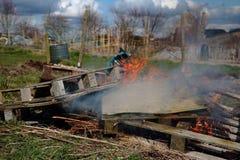 Páletes de madeira e desperdícios gerais que estão sendo queimados imagem de stock