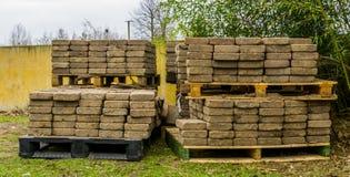 Páletes empilhadas com materiais de construção, pedras de pavimentação em uma pálete, armazenamento para a indústria do pavimento fotos de stock royalty free