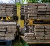 Páletes empilhadas com pedras de pavimentação, materiais de construção, indústria do pavimento fotografia de stock royalty free