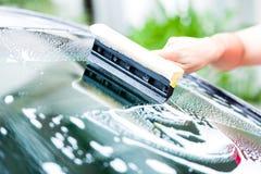 Pára-brisas da limpeza do homem quando lavagem de carros Imagens de Stock