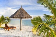 Pára-sol e sunbed em uma praia tropical Imagem de Stock