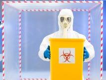 Párroco en el traje protector que lleva a cabo la basura del biohazard Fotos de archivo libres de regalías