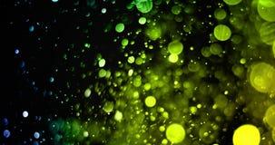 Párticulas de polvo verdes del brillo de la chispa de la pendiente del top en fondo negro con el movimiento el fluir del bokeh, a