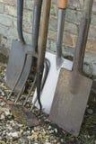 Pás e ferramentas do jardim que inclinam-se na parede de tijolo imagens de stock royalty free