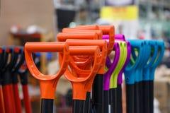 Pás plásticas coloridas do punho nas ferramentas da construção de loja Concentrado fotografia de stock