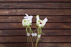 A Páscoa brinca o coelho e a galinha/galo brancos em uma tabela de madeira marrom, teste padrão, lugar para o texto fotos de stock royalty free