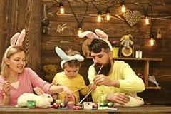 Páscoa Bunny Costume Mãe, ovos da páscoa de pintura do pai fotografia de stock