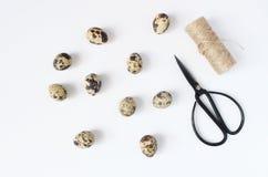 Páscoa, cartão da mola, convite com ovos de codorniz, tesouras pretas e corda natural na tabela branca feminine imagem de stock