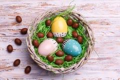 A Páscoa coloriu os ovos no ninho, grama verde contra a cerca de madeira imagens de stock royalty free