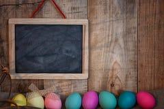 A Páscoa coloriu ovos com curva e a placa preta com espaço da cópia para o texto contra o fundo textured de madeira natural Fotografia de Stock Royalty Free