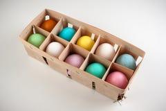 A Páscoa coloriu ovos na caixa de madeira isolados Foto de Stock Royalty Free