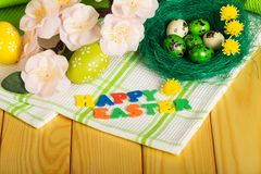 PÁSCOA FELIZ da inscrição, ovos da páscoa coloridos, flores, toalha imagens de stock