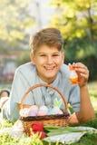Páscoa feliz! O adolescente de sorriso bonito do menino na camisa azul guarda a cesta com os ovos coloridos feitos a mão na grama fotografia de stock