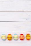 Páscoa feliz! Ovos coloridos da Páscoa no fundo de madeira branco Vista superior com espaço da cópia imagens de stock