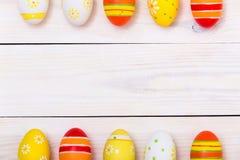 Páscoa feliz! Ovos coloridos da Páscoa no fundo de madeira branco Vista superior com espaço da cópia imagem de stock