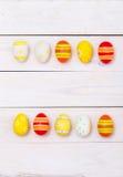 Páscoa feliz! Ovos coloridos da Páscoa no fundo de madeira branco Vista superior com espaço da cópia fotos de stock royalty free