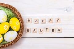 Páscoa feliz! Ovos da páscoa no ninho no fundo de madeira branco Vista superior com espaço da cópia imagem de stock