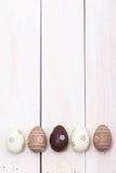 Páscoa feliz! Ovos da páscoa pintados na cor pastel no fundo de madeira branco Vista superior com espaço da cópia fotos de stock