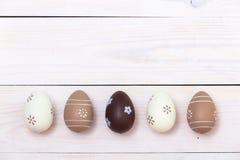 Páscoa feliz! Ovos da páscoa pintados nas cores pastel no fundo de madeira branco Vista superior com espaço da cópia imagens de stock royalty free