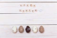 Páscoa feliz! Ovos da páscoa pintados nas cores pastel no fundo de madeira branco Vista superior com espaço da cópia foto de stock royalty free