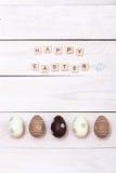 Páscoa feliz! Ovos da páscoa pintados nas cores pastel no fundo de madeira branco Vista superior com espaço da cópia fotos de stock royalty free